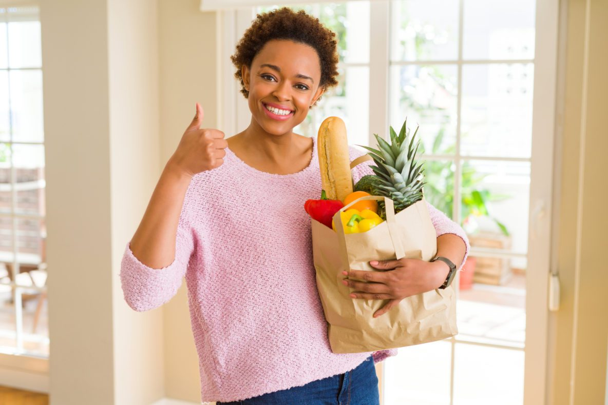 Woman with food shop holding thumbs up