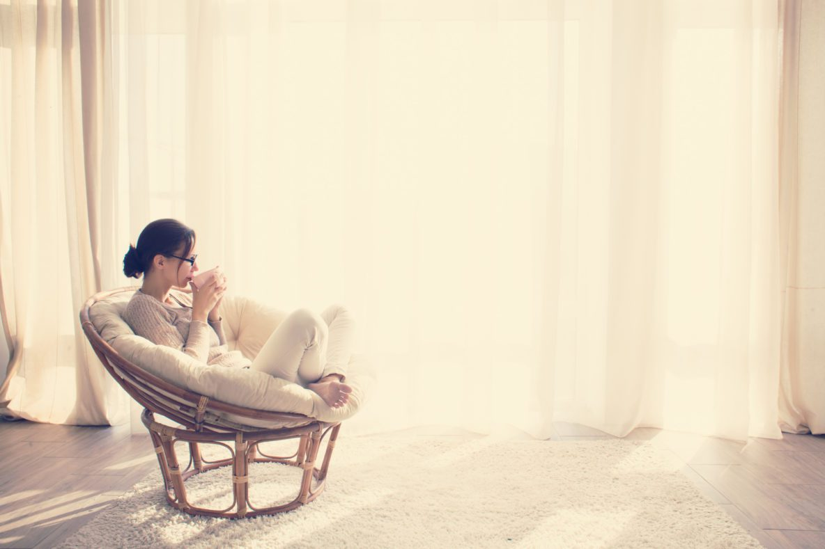 Young woman at home sitting on modern chair in front of window relaxing in her lliving room reading book and drinking coffee or tea